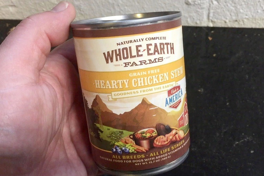 Whole Earth Farms Hearty Chicken Ster Dog Food in Man Hand